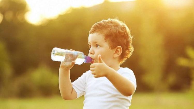 На фото малыш пьет вкусную воду и показывает большой палец вверх