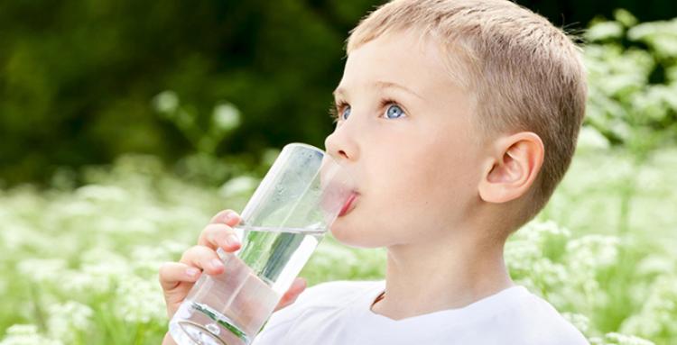 На фото маленький мальчик, который пьет чистую воду из стакана