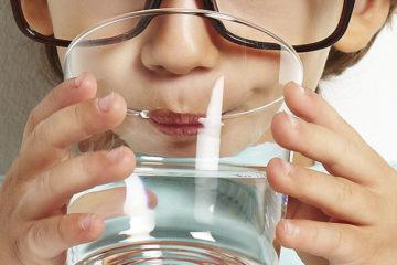 На фотографии мальчик пьет качественную питьевую воду от компании по доставке питьевой бутилированной воды в Черкассах