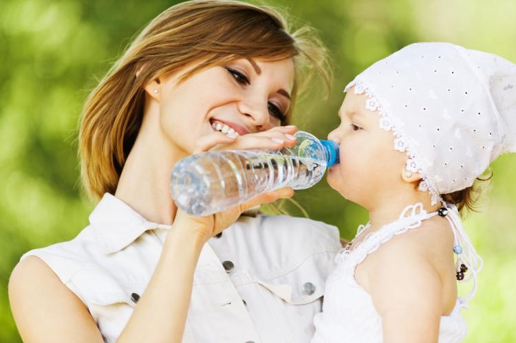 На фото мама держит своего малыша и поит его вкусной водой