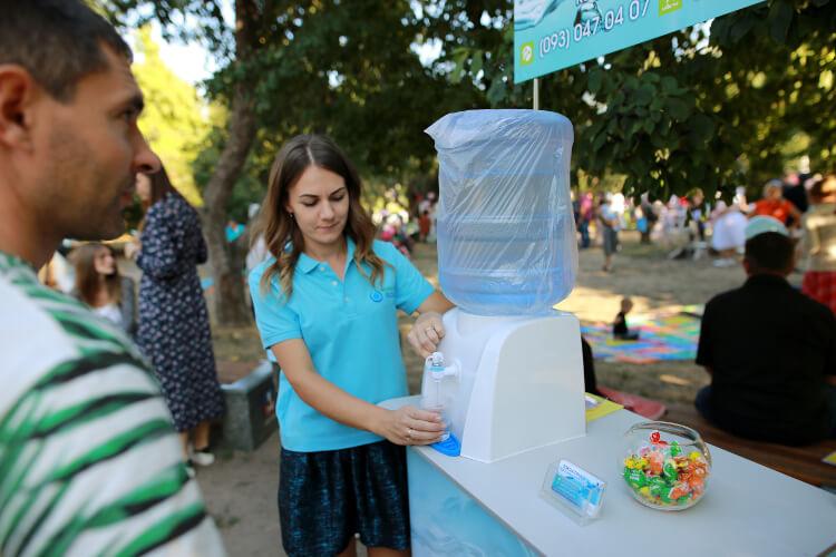 На фото работница компании «Корисна вода» по доставке питьевой воды на дом и офис бесплатно раздает воду на фестивале в Черкассах