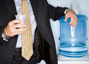 на фото работник офиса с бутылем воды доставленным компанией Корисна вода, бутилированная питьевая вода в офис в Черкассах