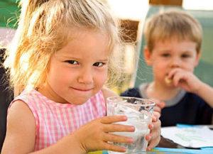На фото девочка держит стакан с очищенной, питьевой водой, доставленной в детский сад или школу в Черкассах